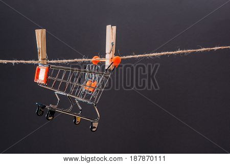 Close-up View Of Small Shopping Cart Hanging On Rope Isolated On Grey, Big Sale Concept