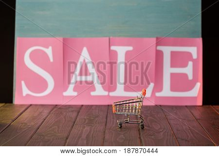 Small Shopping Cart With Sale Sign On Wooden Table, Offer Sale Concept