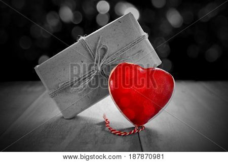 beautiful figurine red heart and gift on black and white background