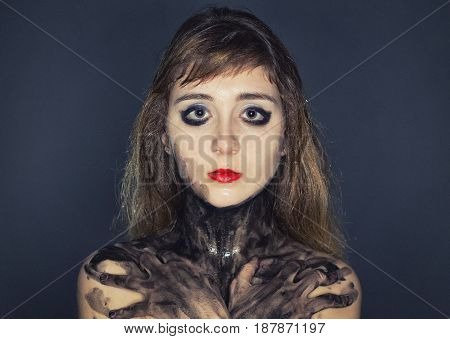 Sad young woman with dirty arms crossed on dark background