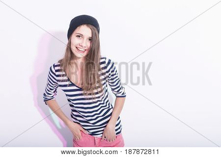 Natural Portrait of Happy Laughing Caucasian Brunette Girl in Hat and Striped Shirt. Posing Against White Background.Horizontal Image