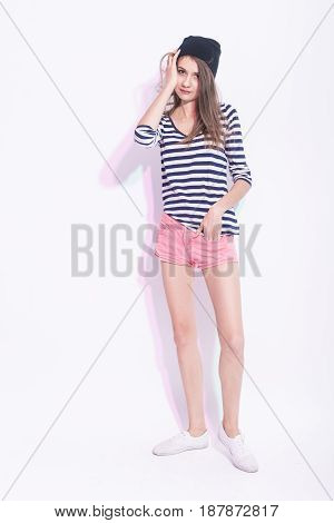 Youth Lifestyle Concepts and Ideas. Full Length Portrait of Caucasian Brunette Girl in Hat and Striped Shirt. Hands Lifted and Touching Head. Vertical Image