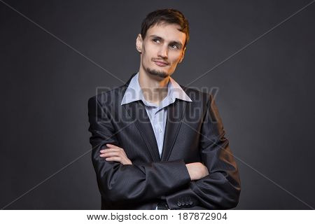 Thoughtful businessman with arms crossed on gray background