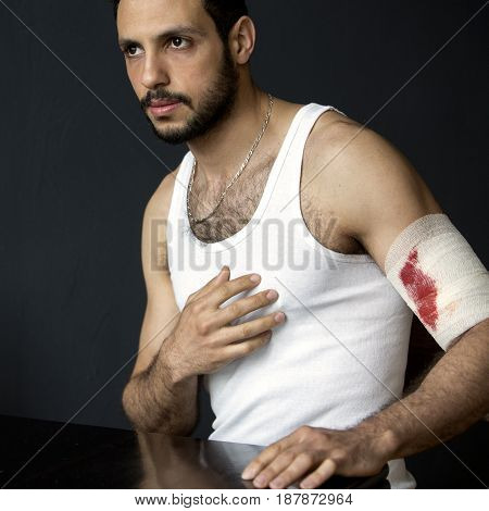 portrait of handsome man with bloody bandage at his arm