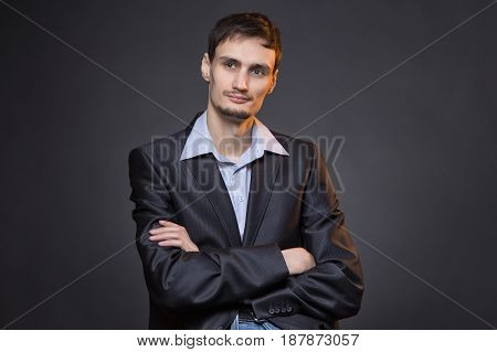 Dreaming businessman with arms crossed on gray background