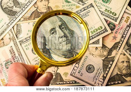 Hundred dollar bill under a magnifying glass is being inspected