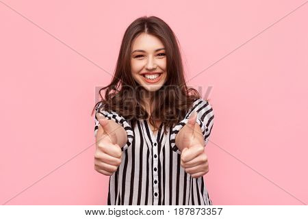 Young brunette in striped shirt showing thumbs up and smiling at camera on pink background.