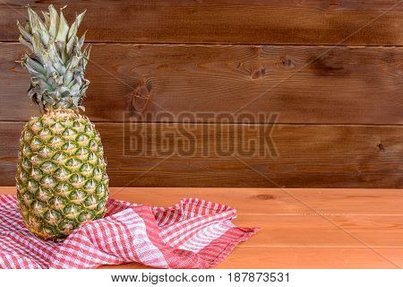 Ripe pineapple lies on the edge on a red towel against the background of a wooden wall.