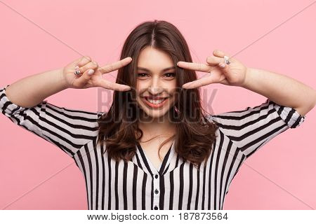 Smiling brunette showing two fingers with both hands and looking at camera on pink.