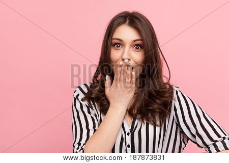 Pretty girl looking excited covering mouth with hand and looking at camera on pink.