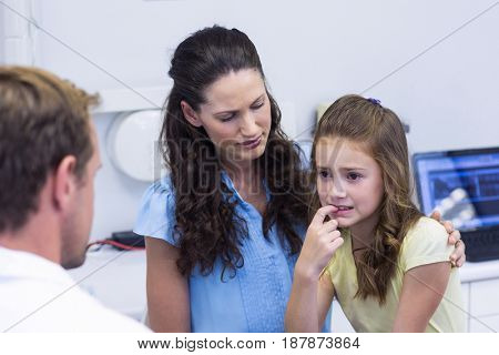 Young patient showing teeth to dentist in dental clinic