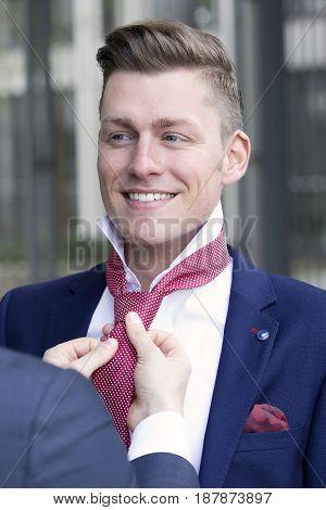 portrait of handsome blond man being helped by adjusting his tie