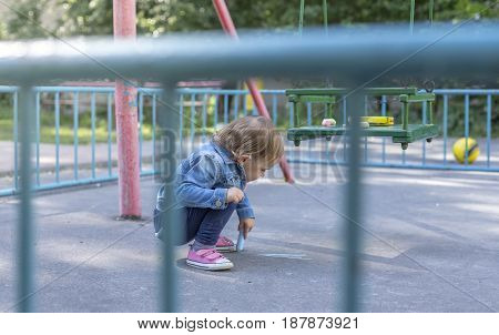 Little beautiful girl in a jeans jacket draws with colored chalks on the playground.