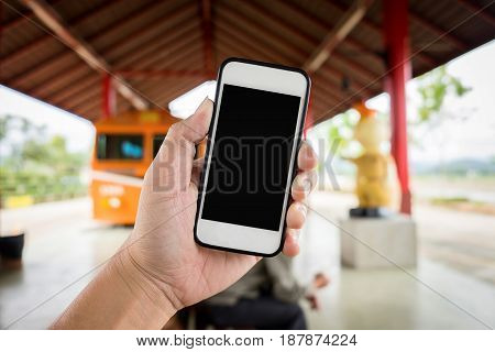 Left hand holding using smartphone with blank screen on Abstract blur background of trainstation.
