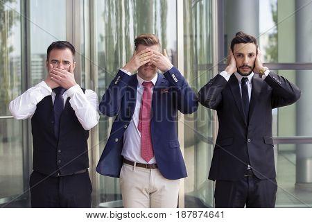 three handsome businessmen as the three wise monkeys