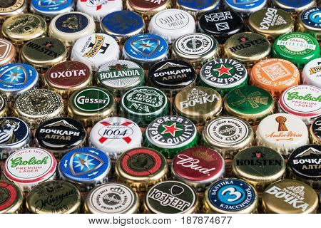 Moscow, Russia - April 13, 2017: Background of beer bottle caps, a mix of various global brands: Grolsch, Bud, Bavaria, Miller, tsingtao corona extra budweiser etc.