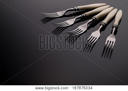 Set of forks on  gray background. Five  pieces