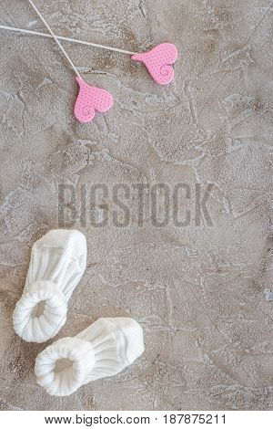 presents set for baby shower with shoes on gray stone background top view mockup