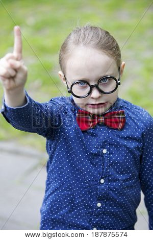 young boy with big glasses lifting his finger and looking serious