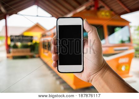right hand holding using smartphone with black screen on Abstract blur background of trainstation.