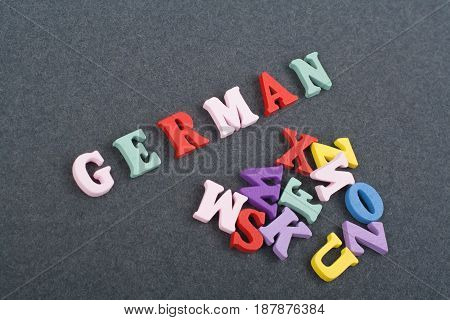 German word on black board background composed from colorful abc alphabet block wooden letters, copy space for ad text. Learning english concept