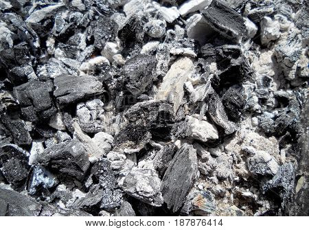 Photo of fire ashes dark grey black coals background texture.Wood burning in the ashes coal.Coal flame fires cooking barbecue.Ashes mineral cube stone bbq grill gray flaming hot charcoal briquettes.