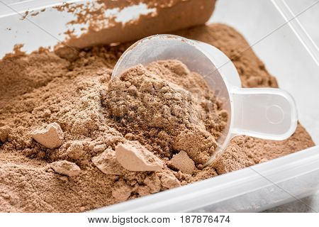 Fitness nutrition with scoop on stone table background
