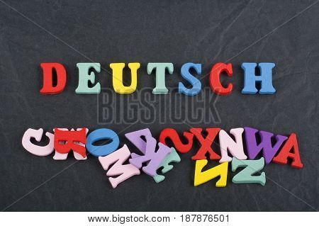 DEUTSCH word on black board background composed from colorful abc alphabet block wooden letters, copy space for ad text. Learning english concept