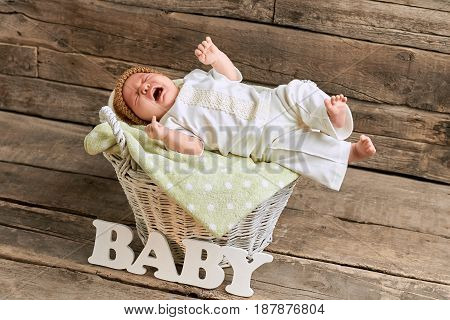 Basket with crying baby. Small child on wooden background. Loud voice of new generation.