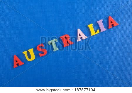 AUSTRALIA word on blue background composed from colorful abc alphabet block wooden letters, copy space for ad text. Learning english concept