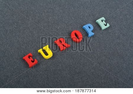 EUROPE word on black board background composed from colorful abc alphabet block wooden letters, copy space for ad text. Learning english concept