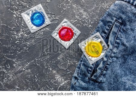 male contraception for safe sex with condoms and jeans on dark desk background top view