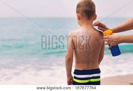 Little boy with suncream on shoulder at beach