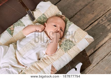 Infant with hand in mouth. Small kid lying on blanket. Baby hunger signs.