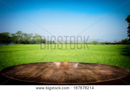 Selected focus empty brown wooden table and cornfield or meadow blur background with bokeh image. for your photomontage or product display.