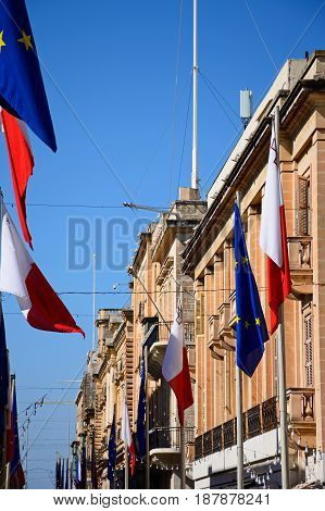 VALLETTA, MALTA - MARCH 30, 2017 - EU and Maltese flags and buildings along Republic Street aka Triq Ir Repubblika Valletta Malta Europe, March 30, 2017.