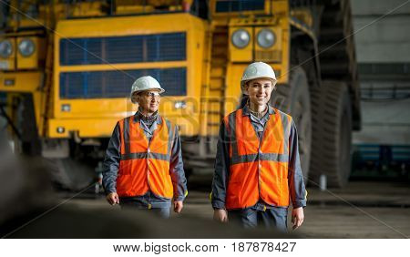 mining workers in front of a huge truck