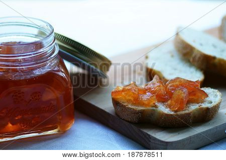 Jar with jam and slice of bread on a wooden board