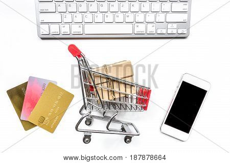 online purchasing with mini trolley, cards and phone on white office desk background top view mock up