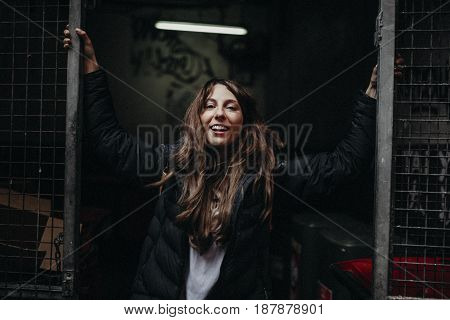 Urban lifestyle portrait of woman holding arms in a fence.