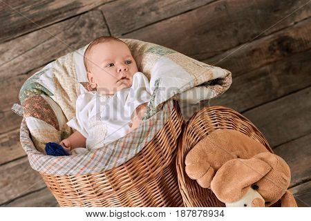 Baby boy in a basket. Cute small kid. Infant behavior and development.