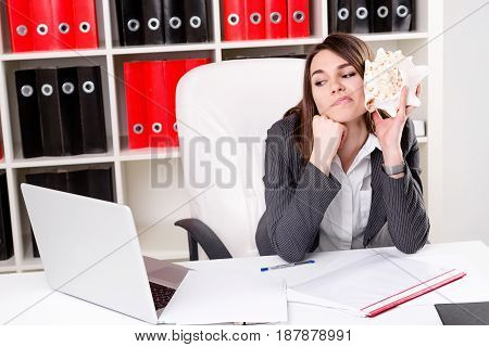 portrait of cute young woman sitting in the office while working and dreaming about vacation on islands