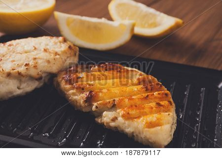 Halloumi roasted on grill cypriot cheese served with lemon slices on wooden desk, close-up, selective focus