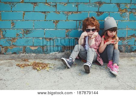 photo of two cute hipsters sitting on floor