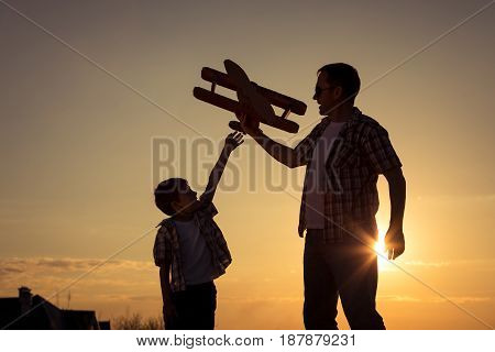 Father And Son Playing With Cardboard Toy Airplane In The Park At The Sunset Time.