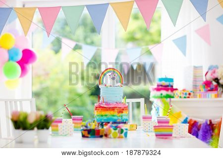Kids birthday party decoration and cake. Decorated table for child birthday celebration. Rainbow unicorn cake for little girl. Room with festive balloons colorful banners in baby pastel color.