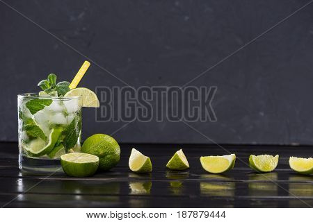 Close-up View Of Mojito Cocktail With Straw In Glass And Lime Slices On Black, Cocktail Drinks Conce