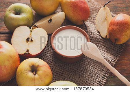 Homemade natural farmer yoghurt for breakfast in jar with fresh fruits - pears and apples on wooden desk, close-up, top view