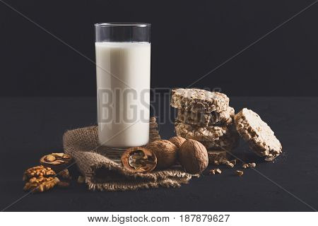 Healthy eating. Glass of milk or yoghurt with nuts and diet crispbreads, still life on black background