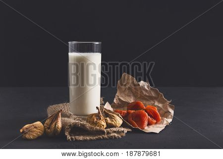 Healthy nutrition. Glass of milk or yoghurt with nuts and diet crispbreads, still life on black background